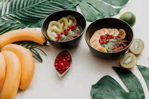 avocat smoothie bol garni de feuilles de chia granola kiwi et dépinards vue du dessus plat feuilles tropicales